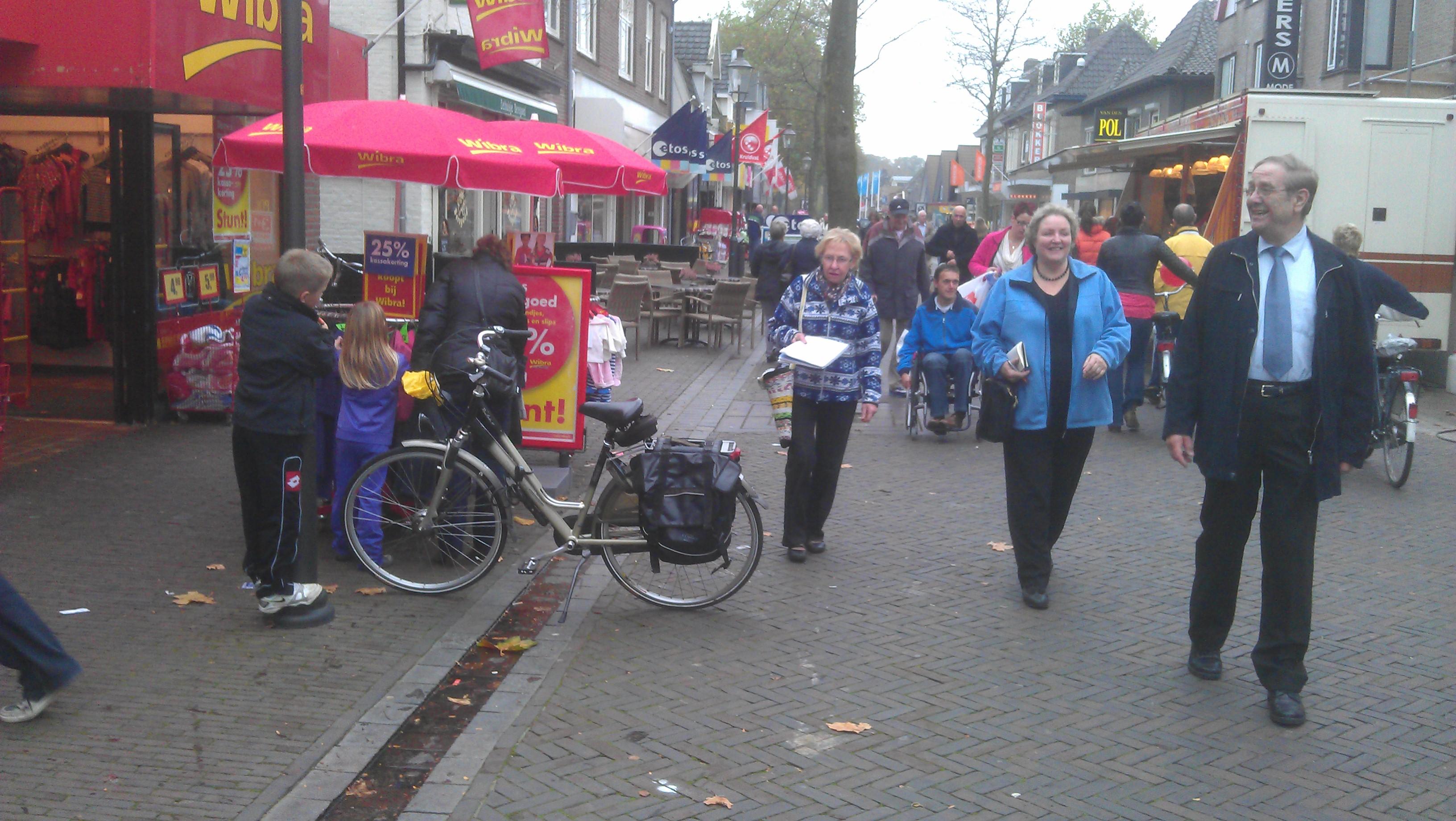 Afbeelding van een winkelstraat met geleidelijn en mensen die lopen te winkelen en een geparkeerde fiets op een geleidelijn.