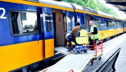 Rolstoel rijdt met behulp van NS assistentie uit de trein het perron op