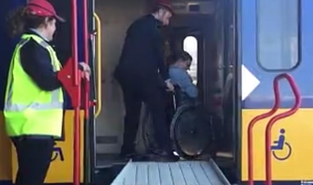 Afbeelding van een man die met behulp van assistentie uit de trein wordt geholpen.
