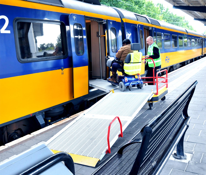 Afbeelding van een NS trein met brug en assistentie om een elektrische rolstoel in de trein te helpen.