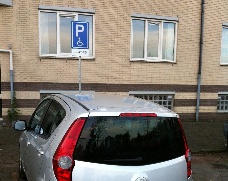 Afbeelding van een auto geparkeerd op een Gehandicapten Parkeerplaats met een bord en kenteken.
