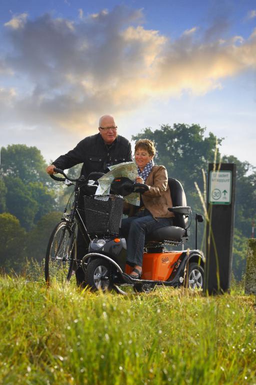 Afbeelding van een (kaart-lezende) vrouw in een scootmobiel met naast haar een man op een fiets.