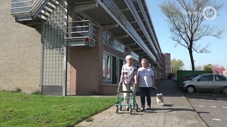 Afbeelding van een vrouw met een rollator aan het wandelen met een hulpverlener in de wijk.