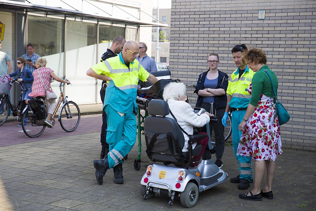 Afbeelding van een vrouw in een scootmobiel na aanrijding omringd door ambulancepersoneel en begeleidster.